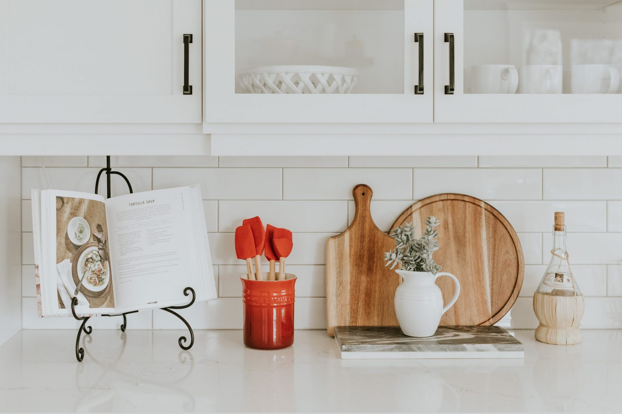 Cook book and cooking utensils on kitchen counter