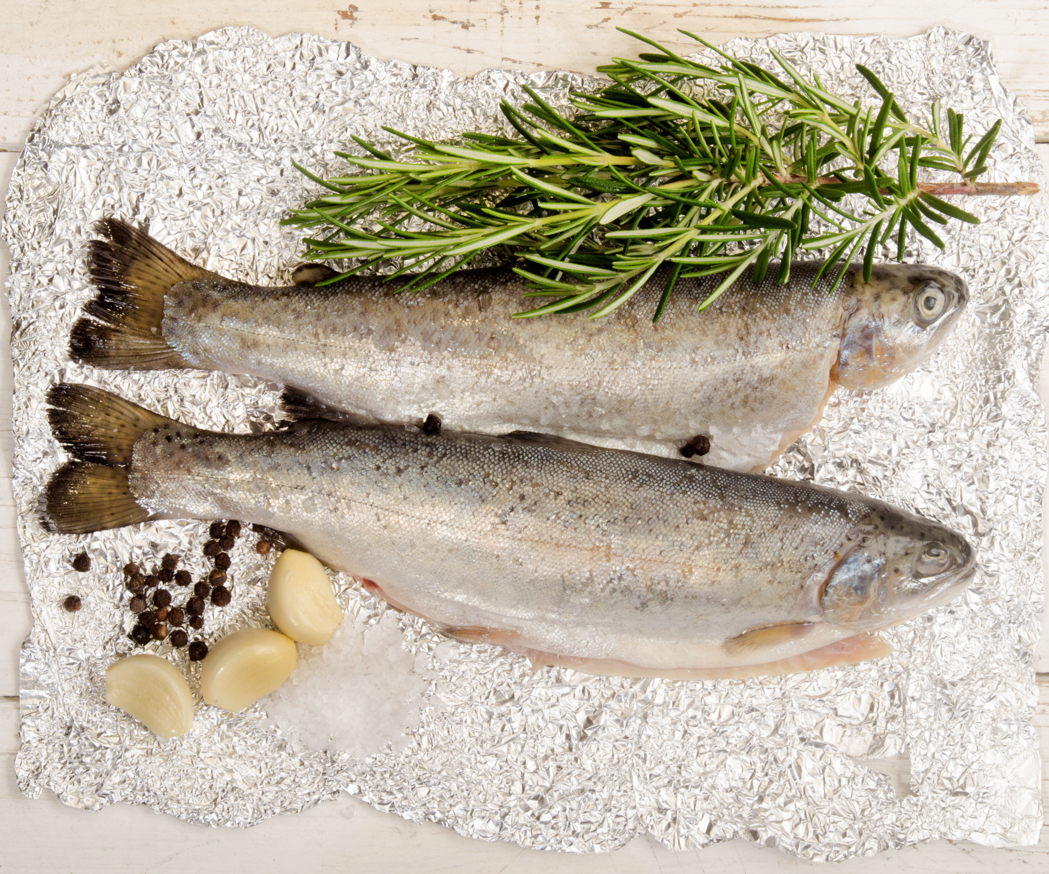 Trout on foil next to garlic, salt and herbs